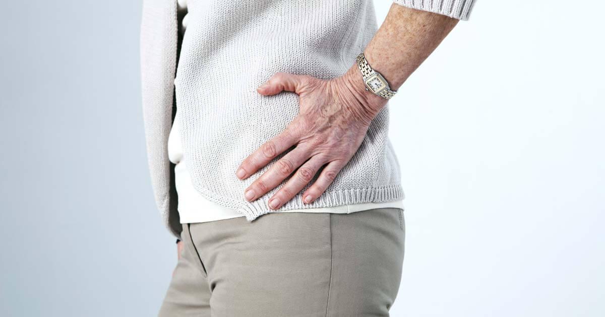 Eine alte Frau hält sich ihre von Hüftarthrose schmerzende Hüfte