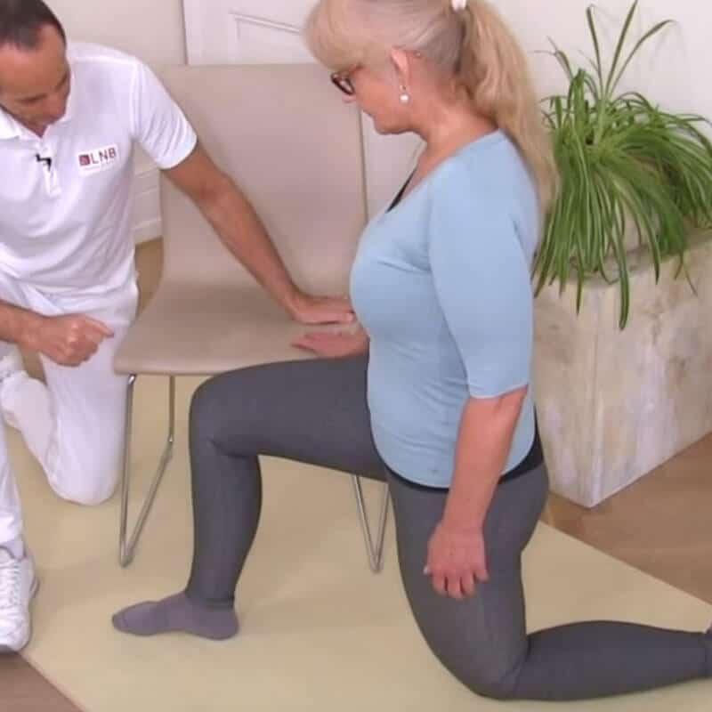 Patientin führt Übung gegen Hüftschmerzen im Ausfallschritt aus