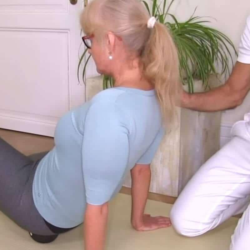 Patientin führt Übung mit Medi-Kugel gegen Hüftschmerzen aus
