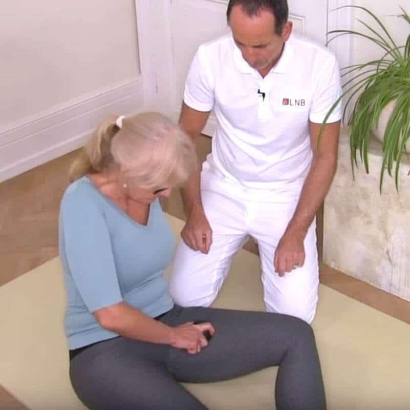 Patientin führt Übung mit Mini-Kugel am inneren Oberschenkel gegen Hüftschmerzen aus