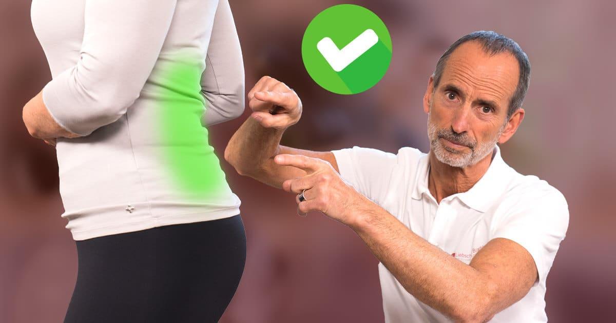 """Roland Liebscher-Bracht zeigt auf den unteren Rücken einer Frau. Dieser ist durch grünes Leuchten hervorgehoben. Über seinen Händen ist das Symbol """"grüner Haken"""""""