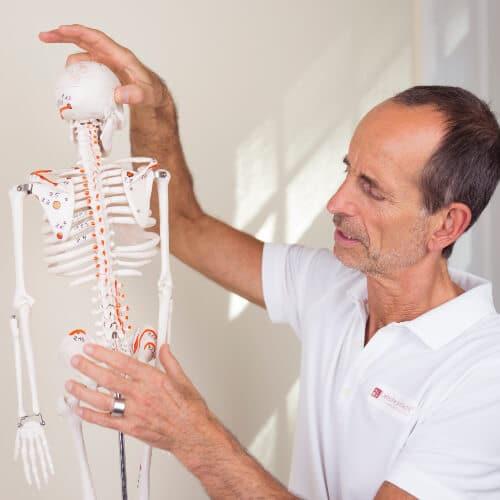 Roland Liebscher-Bracht steht am Skelett mit eingezeichneten Osteopressur-Punkten. Behandlung bei der Kniegelenksarthrose mit der Osteopressur