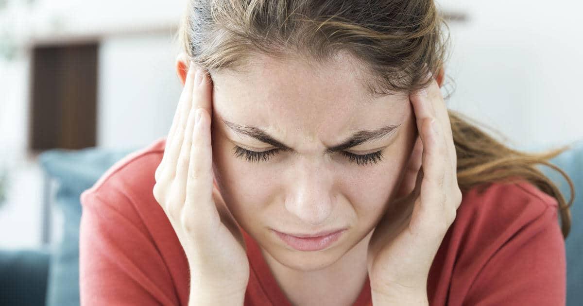 Frau hat starke Kopfschmerzen und Gesichtsschmerzen und greift an die Schläfen