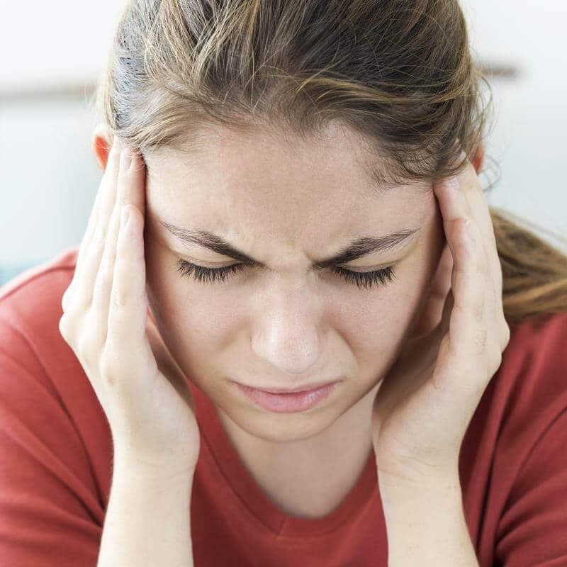 Frau hat starke Kopfschmerzen und hält sich die Schläfe