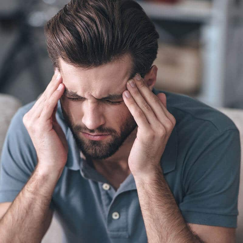 Ein junger Mann hält sich mit beiden Händen seine Stirn, da er Kopfschmerzen in Folge eines HWS-Syndroms hat