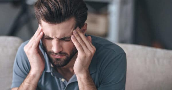 Mann hält sich den Kopf bei starken Kopfschmerzen und Gesichtsschmerzen
