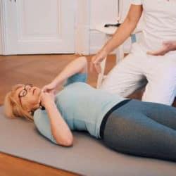 Schmerzspezialist Roland Liebscher-Bracht zeigt einer Patientin eine Faszien-Rollmassage gegen Schulterschmerzen, bei der die Mini-Kugel zum Einsatz kommt