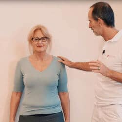 Eine Frau führt eine Faszien-Rollmassage an der Wand am Schulterblatt aus, um eine Frozen Shoulder zu behandeln