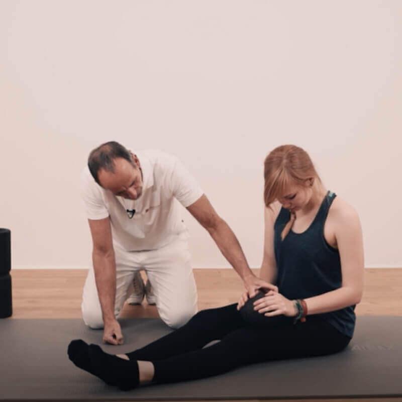 Schmerzspezialist Roland Liebscher-Bracht zeigt einer jungen Frau eine Faszien-Rollmassage mit der Kugel-Rolle am vorderen Oberschenkel
