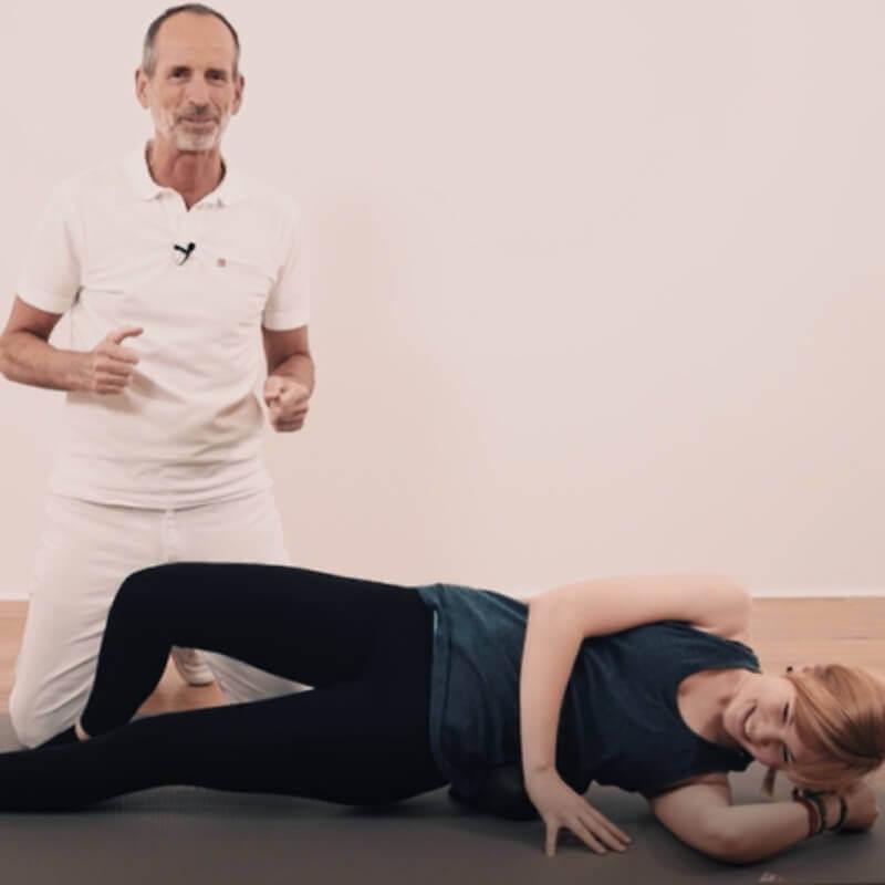 Eine Frau liegt seitlich auf einer Matte, mit dem Oberkörper auf einer Kugel-Faszienrolle. Ein Bein ist leicht angewinkelt. Roland Liebscher-Bracht kniet hinter ihr und erklärt etwas.