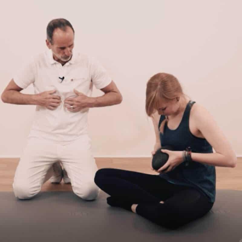 Schmerzspezialist Roland Liebscher-Bracht zeigt einer jungen Frau eine Faszien-Rollmassage mit der Kugel-Faszienrolle am Zwerchfell