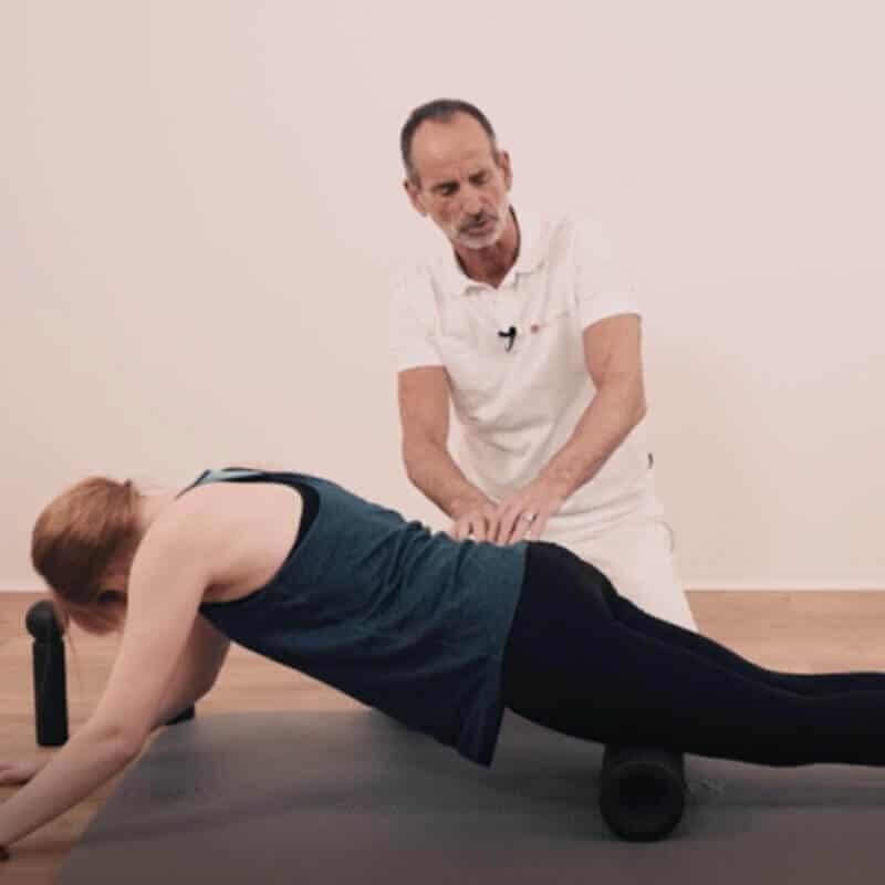 Schmerzspezialist Roland Liebscher-Bracht zeigt einer jungen Frau eine Faszien-Rollmassage mit der MAXI-Faszienrolle an den Oberschenkeln.