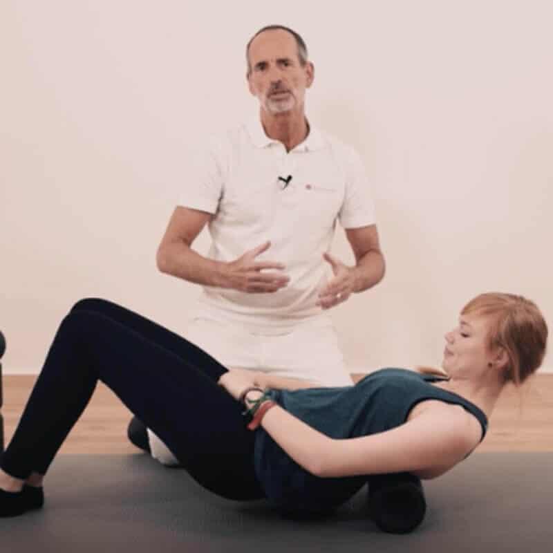 Schmerzspezialist Roland Liebscher-Bracht zeigt einer jungen Frau eine Faszien-Rollmassage mit der MAXI-Faszienrolle am Ruecken.