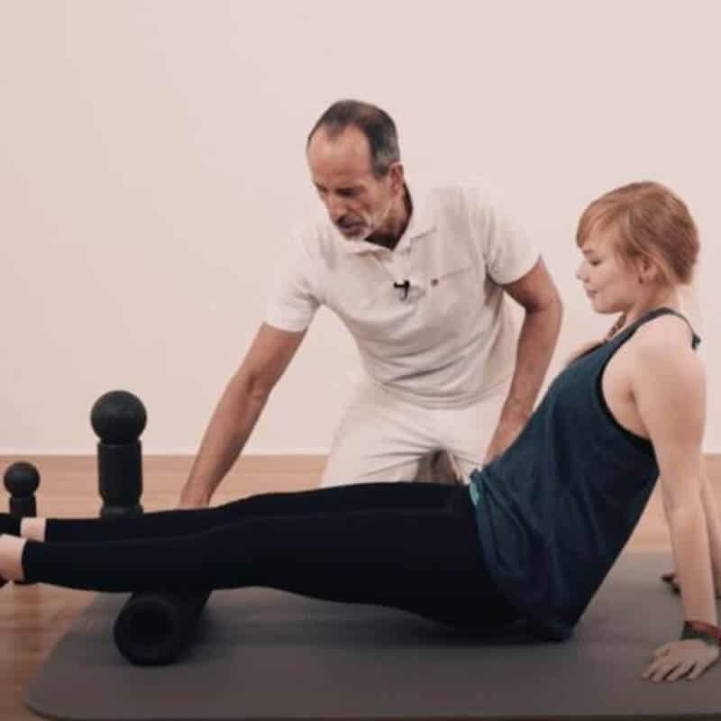 Schmerzspezialist Roland Liebscher-Bracht zeigt einer jungen Frau eine Faszien-Rollmassage mit der Maxi-Rolle an den Waden