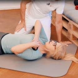 Eine Frau führt eine Faszien-Rollmassage im Brustbereich aus, um eine Frozen Shoulder zu behandeln