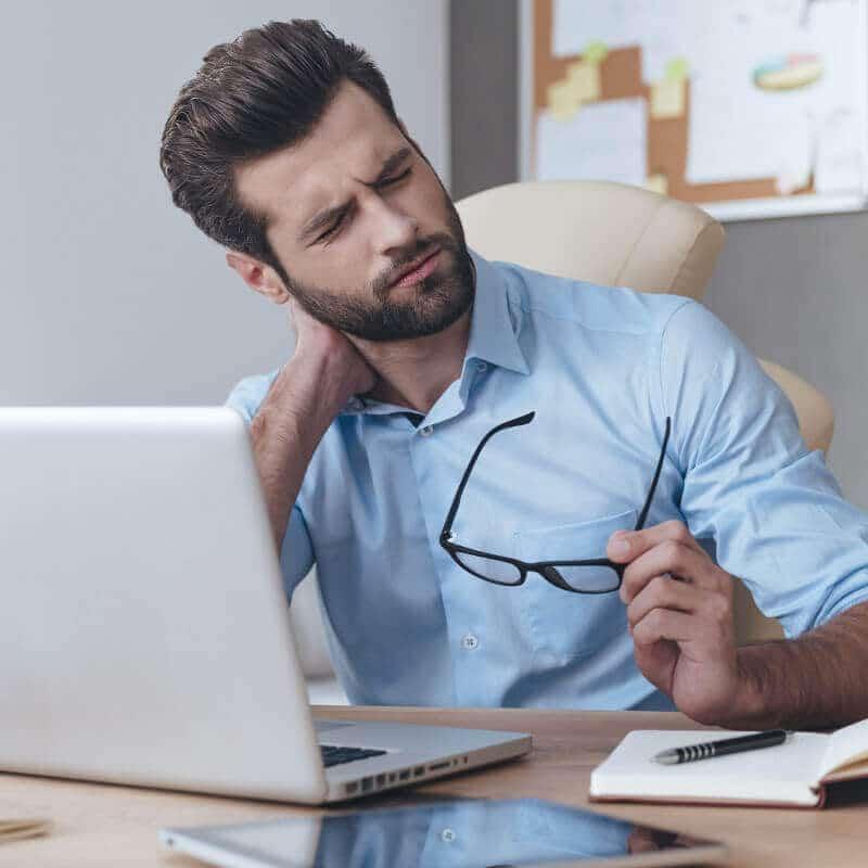 Ein Mann sitzt mit Nackenschmerzen im Büro vor seinem Laptop