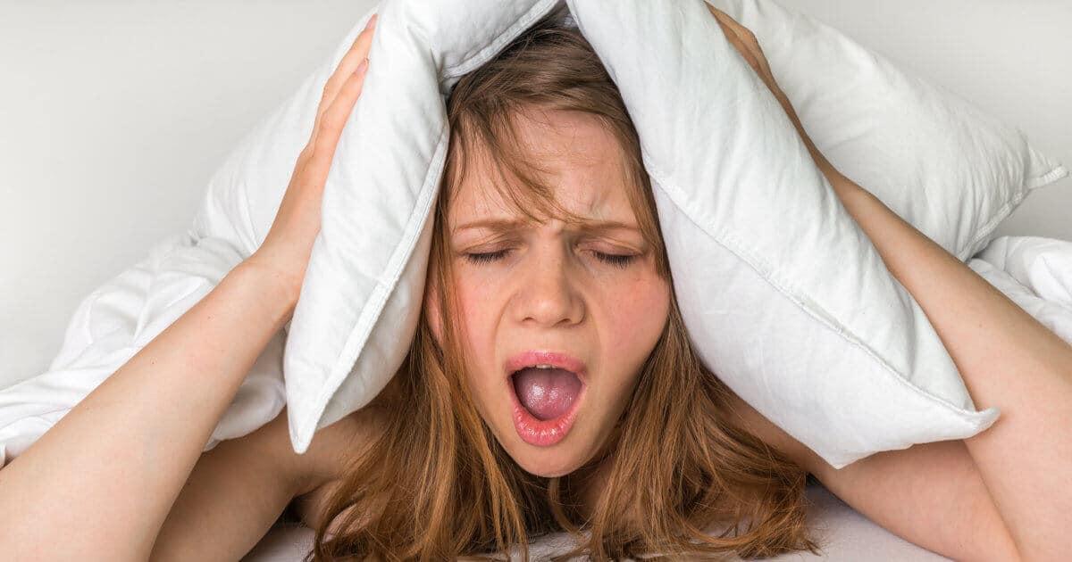 Eine junge Fraue hat Migräne und Gesichtsschmerzen und hält sich schreiend mit einem Kissen ihre Ohren zu