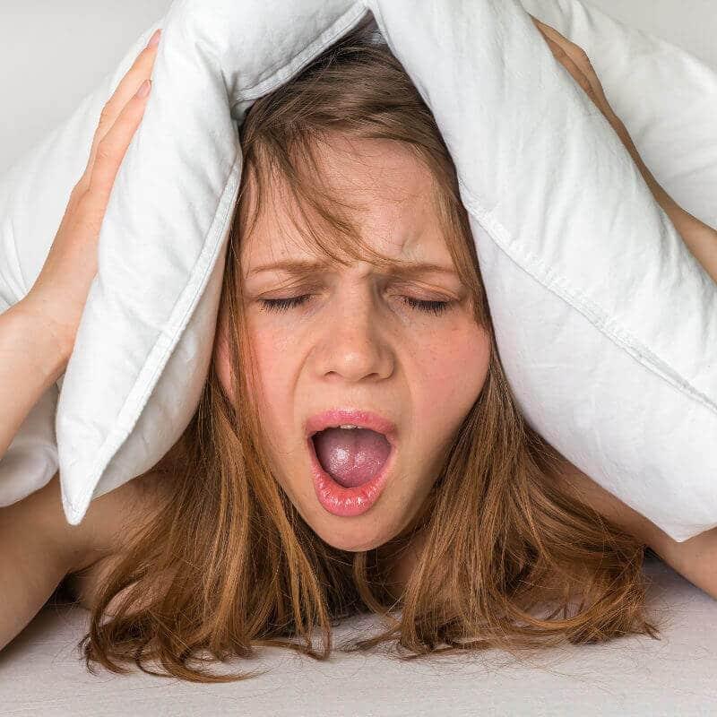 Eine junge Fraue hat Migräne und hält sich schreiend mit einem Kissen ihre Ohren zu