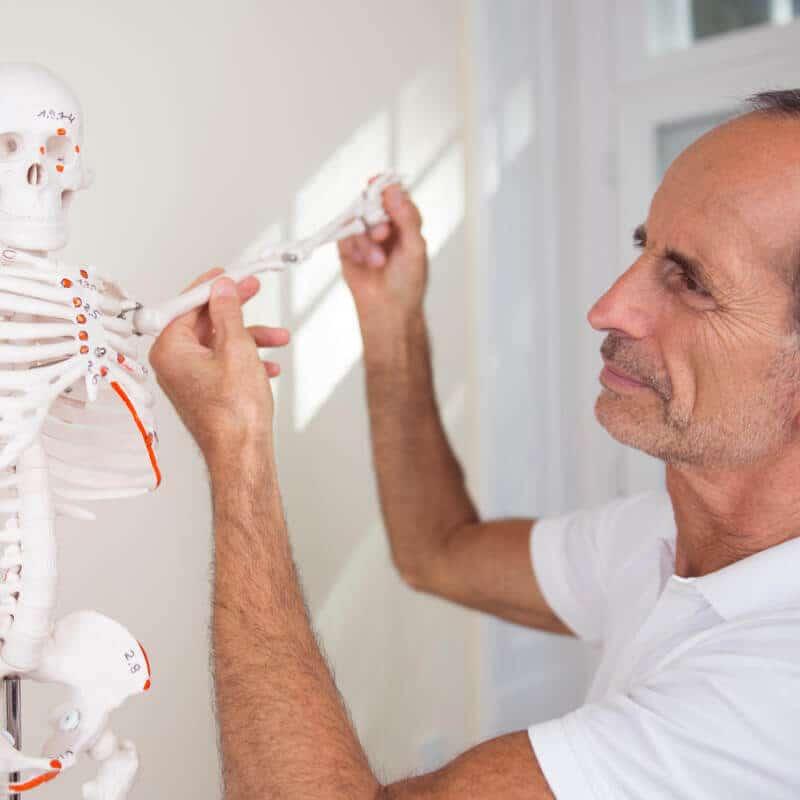Schmerzspezialist Roland Liebscher-Bracht demonstriert am Skelett die Osteopressurpunkte bei Schulterschmerzen