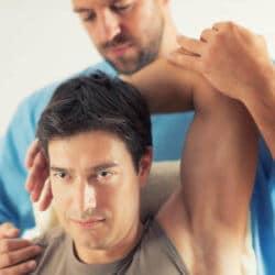 Ein Physiotherapeut mobilisiert den Nacken eines Mannes