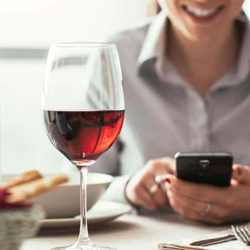 Eine Frau in einem Restaurant bedient ihr Smartphone, vor ihr steht ein Glas Rotwein