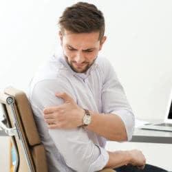 Ein Mann hält sich im Büro seine schmerzende Schulter