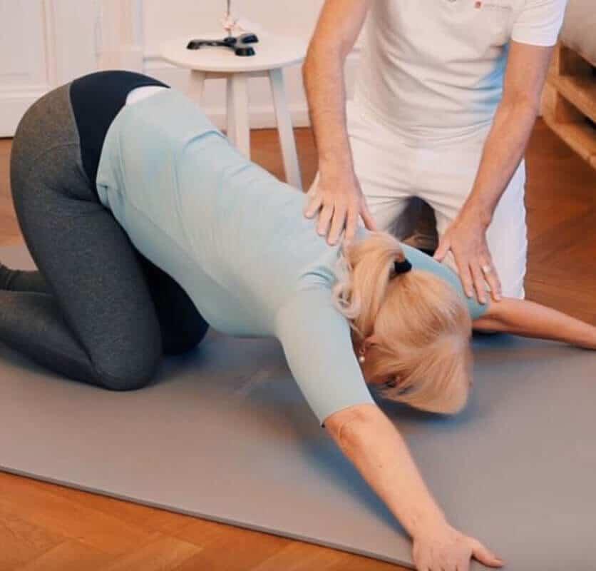 Schmerzspezialist Roland Liebscher-Bracht zeigt einer Patientin eine Dehnübung gegen Schulterschmerzen, bei der die Schulterrückseite aufgedehnt wird.
