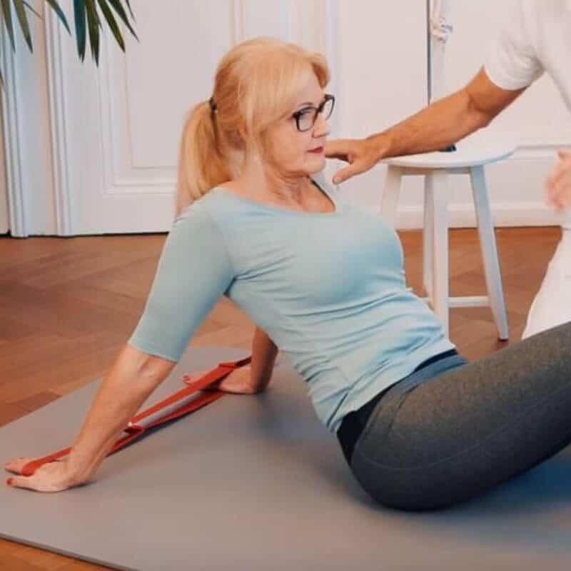 Schmerzspezialist Roland Liebscher-Bracht zeigt einer Patientin eine Dehnübung gegen Schulterschmerzen, bei der die Schultervorderseite mithilfe der Übungsschlaufe aufgedehnt wird.