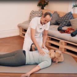 Schmerzspezialist Roland Liebscher-Bracht zeigt einer Patientin eine Dehnübung zur Behandlung einer Frozen Shoulder