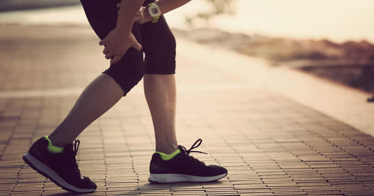 Frau greift sich beim Joggen in die Kniekehle. Die Schmerzen können mit Patellasehnen-Schmerzen einhergehen