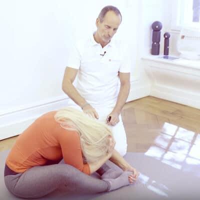 Eine Frau sitzt auf einer Matte, Beine leicht herangezogen. Sie beugt sich mit dem Oberkörper in Richtung ihrer Füße. Roland Liebscher-Bracht legt seine Hände auf ihren Rücken.