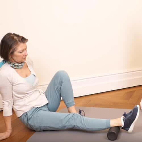Patientin sitzt auf dem Boden und rollt ihre Wade mit der Medi-Rolle aus