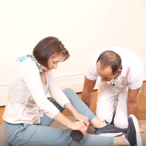 Eine Frau sitzt auf einer Bodenmatte und massiert ihr Schienbein mit einer Medi-Faszienrolle. Roland Liebscher-Bracht kniet neben ihr und beobachtet sie bei der Ausführung der Übung.