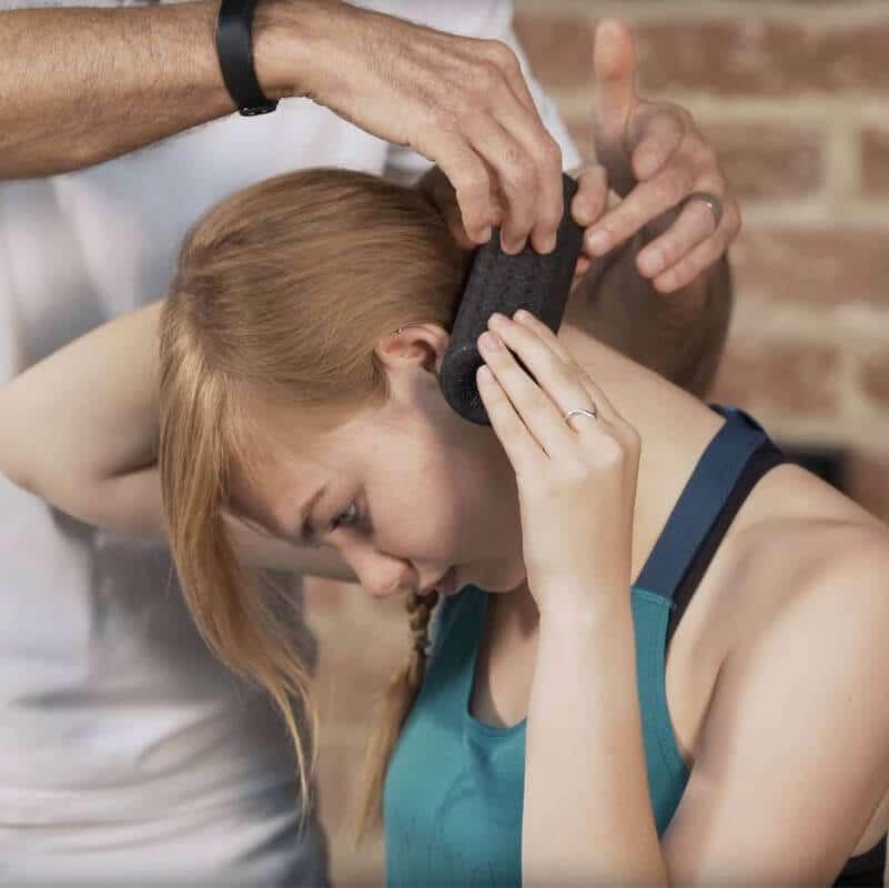 Schmerzspezialist Roland Liebscher-Bracht zeigt einer Patientin eine Faszien-Rolmassage am seitlichen Hals-Nacken-Bereich