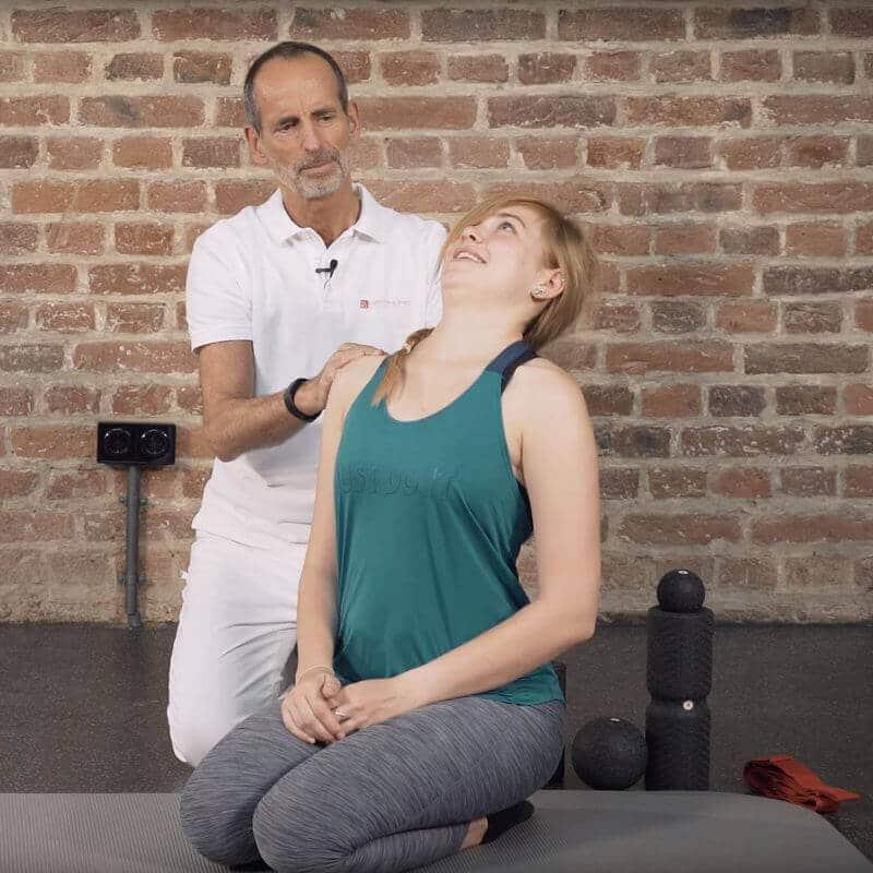 Schmerzspezialist Roland Liebscher-Bracht zeigt einer Patientin eine Dehnübung gegen einen Bandscheibenvorfall in der Halswirbelsäule, bei der diese ihren Kopf nach hinten dehnt