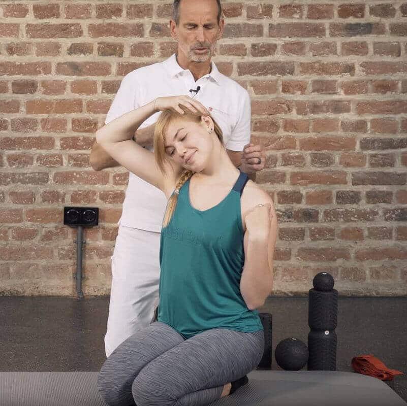 Schmerzspezialist Roland Liebscher-Bracht zeigt einer Patientin eine Dehnübung gegen einen Bandscheibenvorfall in der Halswirbelsäule, bei der diese ihren Kopf seitlich dehnt