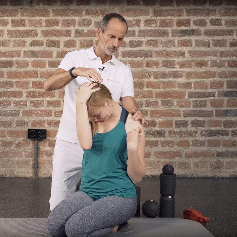 Schmerzspezialist Roland Liebscher-Bracht zeigt einer Patientin eine Dehnübung gegen einen Bandscheibenvorfall in der Halswirbelsäule, bei der diese ihren Kopf nach vorne dehnt