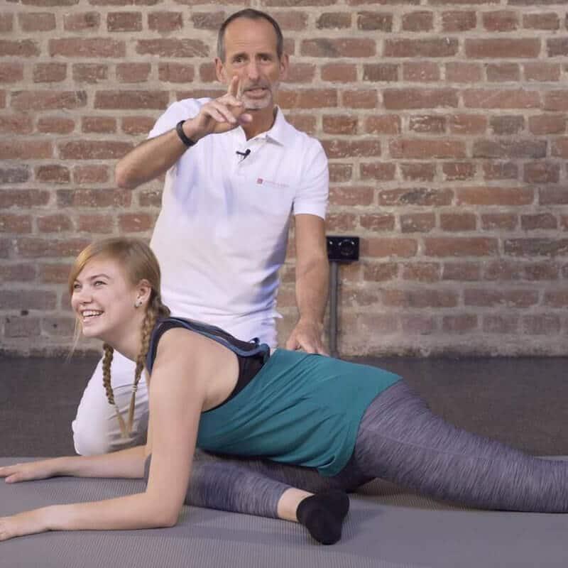 Schmerspezialist Roland Liebscher-Bracht zeigt einer jungen Patienten eine Übung zur Dehnung des Gesäßes bei Beckenschiefstand
