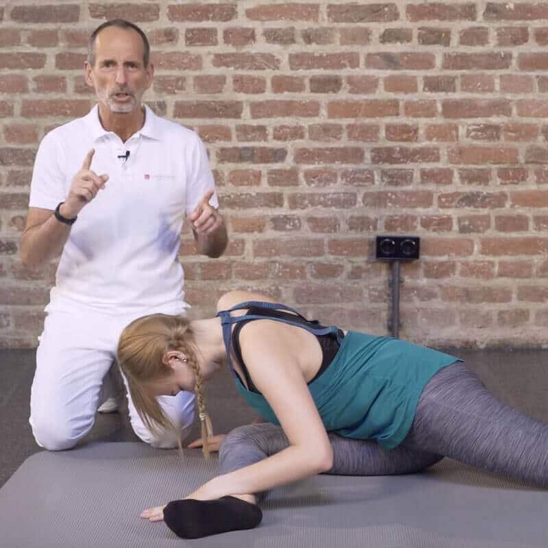 Schmerspezialist Roland Liebscher-Bracht zeigt einer jungen Patienten eine Übung zur noch intensiveren Dehnung des Gesäßes bei Beckenschiefstand