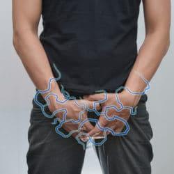 Mann hält sich mit beiden Händen den Leistenbereich
