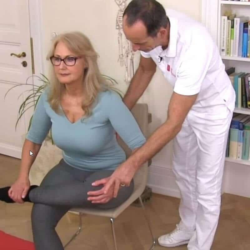 Patientin sitzt auf der Stuhlkante und dehnt ihr Gesäß, indem sie das Bein über das andere schlägt und sich nach vorne lehnt