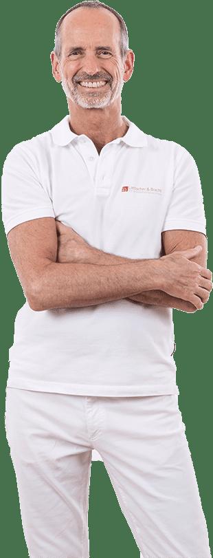 Roland Liebscher - Bracht grinst in weißen Klamotten in die Kamera mit verschränkten Armen und Beinen bis zum Knie