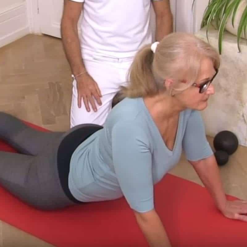 Patientin führt aus dem Vierfüßlerstand ihr Becken Richtung Boden und stützt sich mit durchgestreckten Armen unter ihrem Oberkörper auf. Sie führt die Engpassdehnung aus.