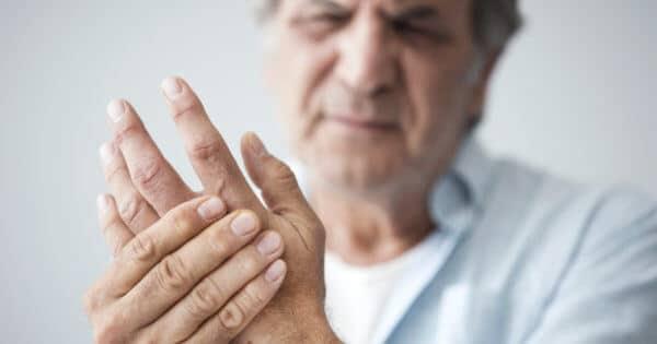 Ein älterer Mann hält sich seine verkrümmten und schmerzenden Finger bei Rheuma