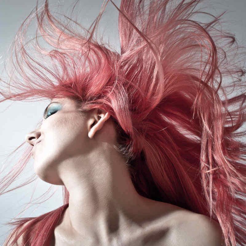Frau schwenkt den Nacken und die Haare fliegen dabei.