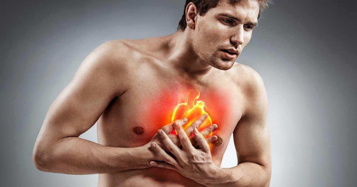Ein Mann fasst sich an die Brust, da er Brustschmerzen und Herzschmerzen hat