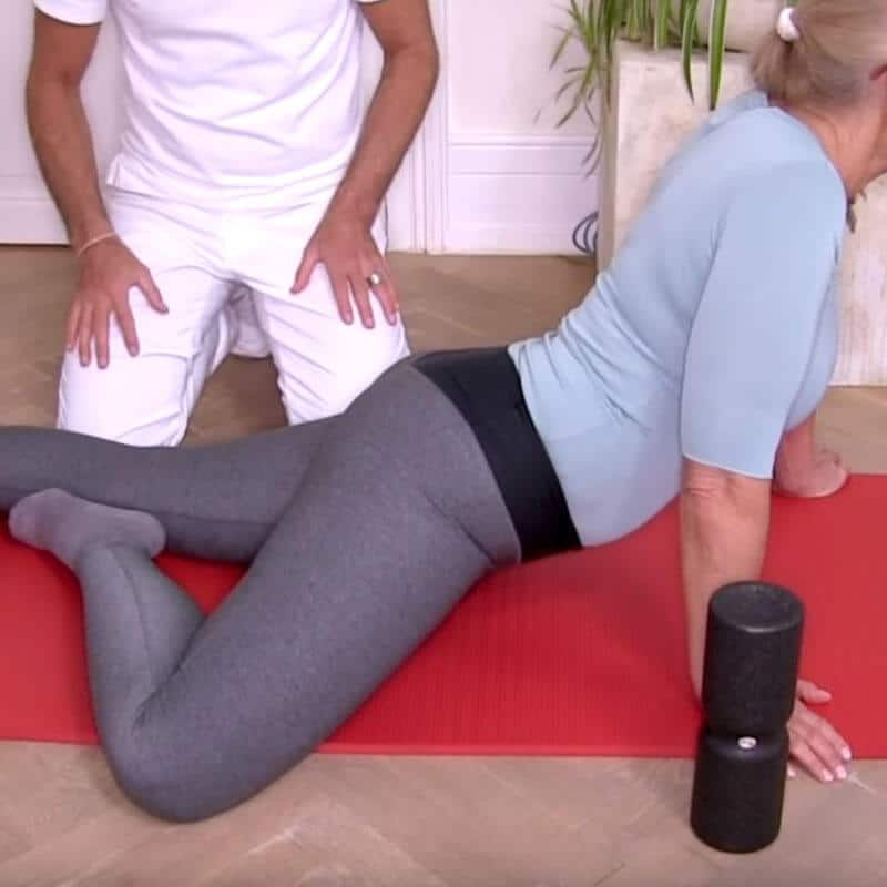Patientin führt die Engpassdehnung mit einem angewinkelten Bein aus