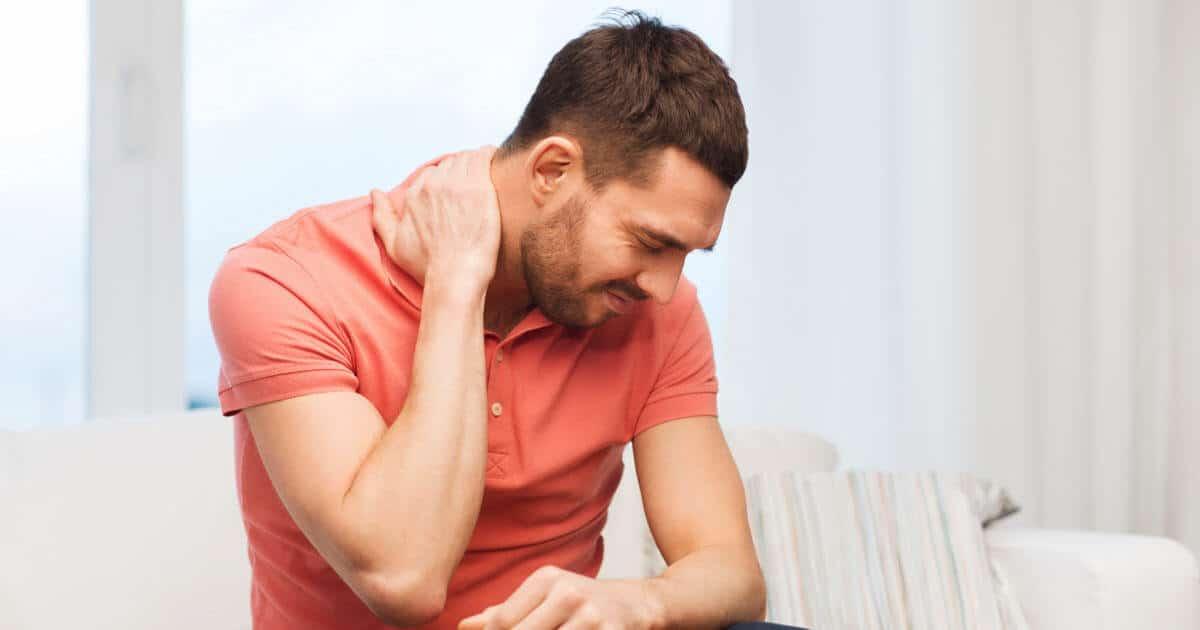 Mann sitzt auf dem Sofa und hält sich den schmerzenden Nacken