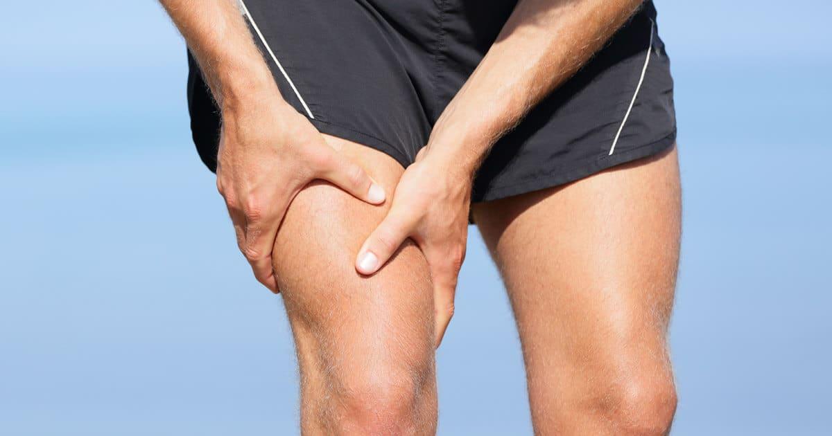 Ein Mann hält sich den Oberschenkel aufgrund von Überlastungen. Diese können zu Patellasehnen-Schmerzen führen