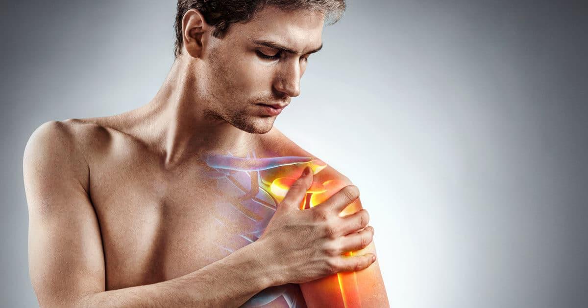 Mann mit Schulterschmerzen hält sich die Schulter